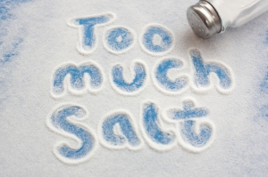 """An image with the words """"too much salt"""" drawn in a spilled pile of salt on a blue surface"""