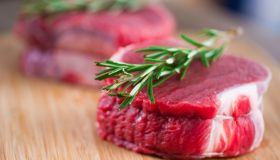 Two pieces of raw beef tenderloin with sprigs of rosemary