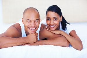 A smiling couple lying on their bed at home