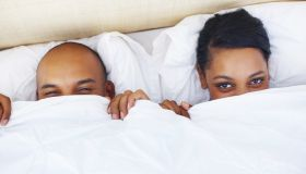 A couple in bed peeking their eyes over the sheets
