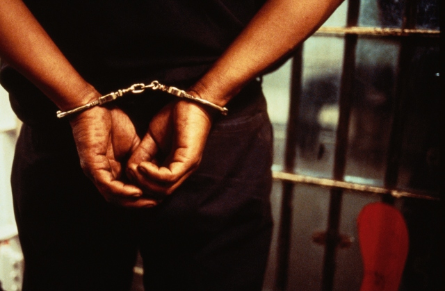 A teen in jail with his hands handcuffed behind his back