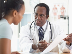 A male doctor pointing to a chart as he talks to his female patient