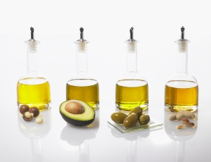 Four bottles of different types of oils in a row