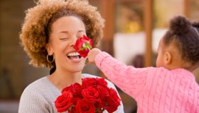 A little girl holding a red rose up to the nose of her smiling mother