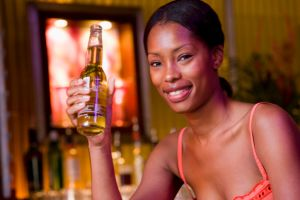 A woman at a bar with a bottle of beer