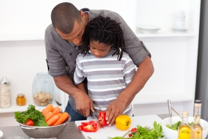 A loving father helping his son cut vegetables in their kitchen