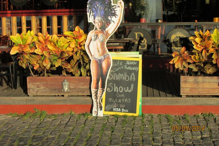 A poster advertising a samba show featuring a black woman in Carnival garb
