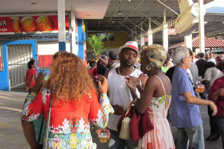 Black men talk to Brazilian women at May 13 celebration.