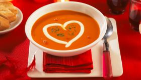 A bowl of tomato soup with a heart made of sour cream