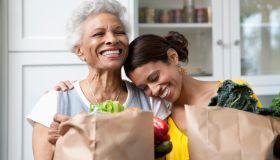A mother and daughter holding grocery bags filled with healthy foods in the kitchen