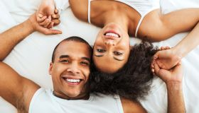 Cheerful couple lying in bed, woman upside down
