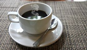 A cup of hot, black coffee in a white cup on a table.