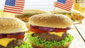Several burgers with an American flag toothpick on top of them