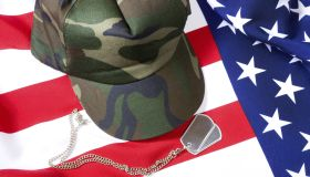 A BDU cap and dog tags sitting on top of the American Flag