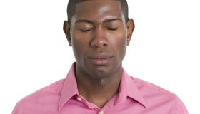 A man wearing a pink shirt with his eyes closed