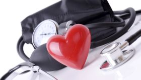 A blood pressure gauge, stethoscope and a red plastic heart