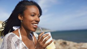 A woman on a beach drinking from a cup with a straw