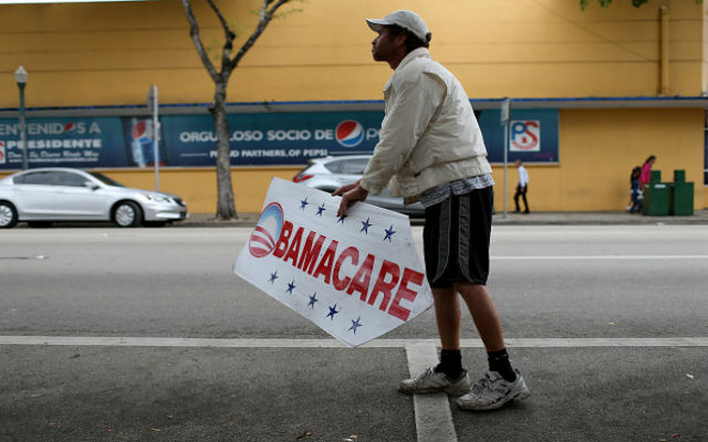 Pedro Rojas holds a sign directing people to an insurance company where they can sign up for the Affordable Care Act, also known as Obamacare, before the February 15th deadline on February 5, 2015 in Miami, Florida. Numbers released by the government show that the Miami-Fort Lauderdale-West Palm Beach metropolitan area has signed up 637,514 consumers so far since open enrollment began on Nov. 15, which is more than twice as many as the next large metropolitan area, Atlanta, Georgia. (Photo by Joe Raedle/Getty Images)
