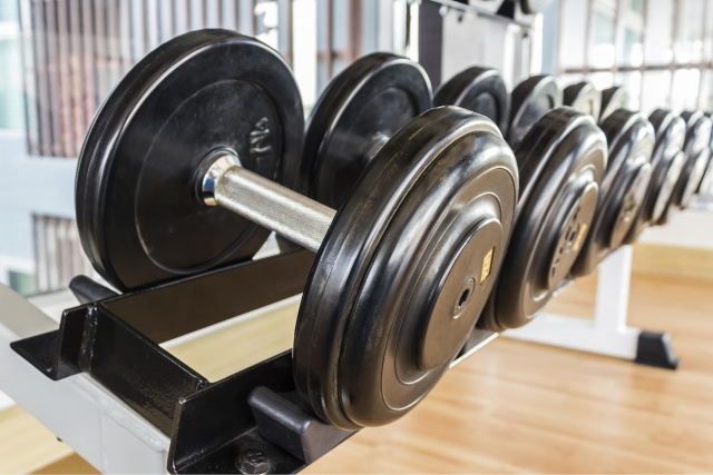 Many black dumbbell lined up in a fitness room.