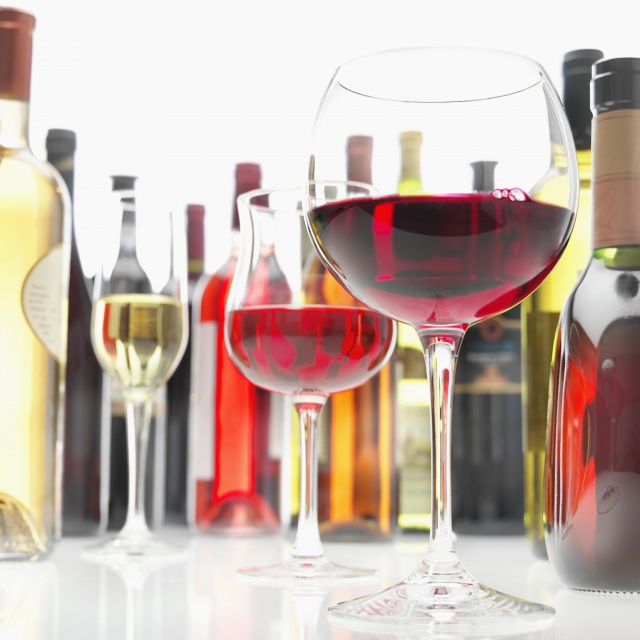 Glasses Of Red And White Wine Encircled By Bottles Of Wines Of Many Kinds, Low View (Focus On Glass Of Red Wine)
