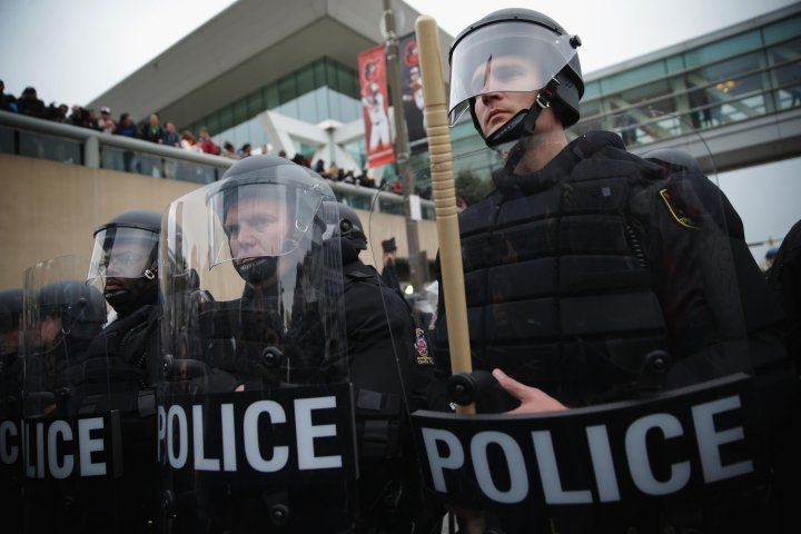 Police in riot gear confront protesters