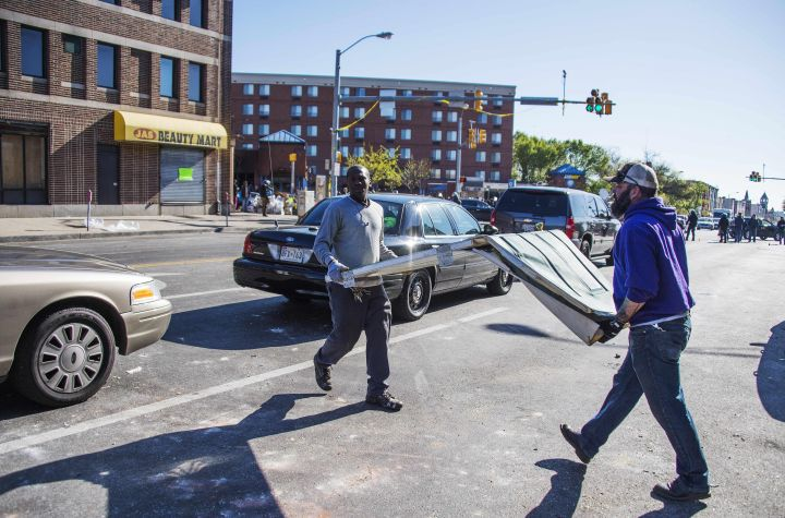 Two men help move a door from a looted store in Baltimore.