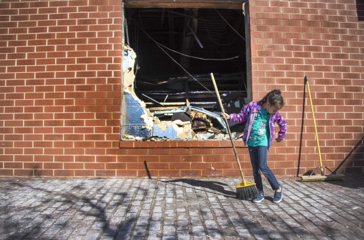 A little girl helps clean up a looted CVS Pharmacy in Baltimore.
