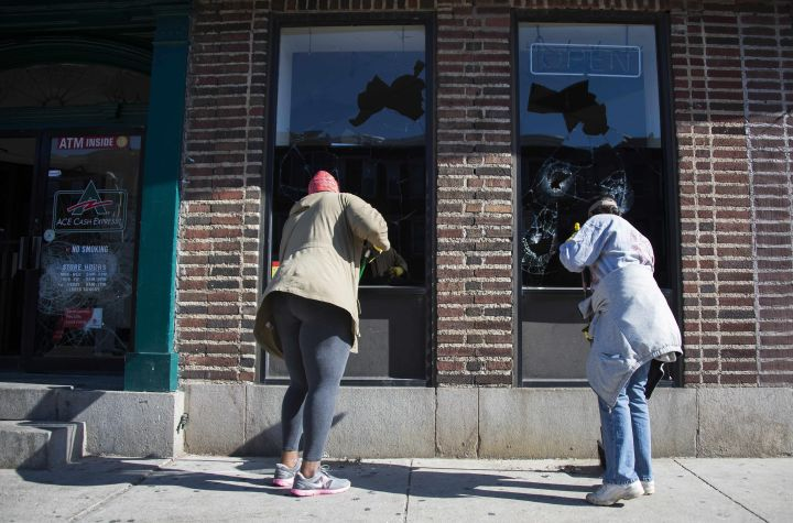 Women take part in recovering Baltimore by cleaning up the front of the local cash checking store.