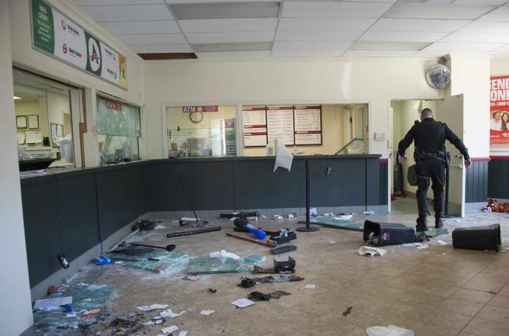 A security officer walks through a looted check cashing store in Baltimore.