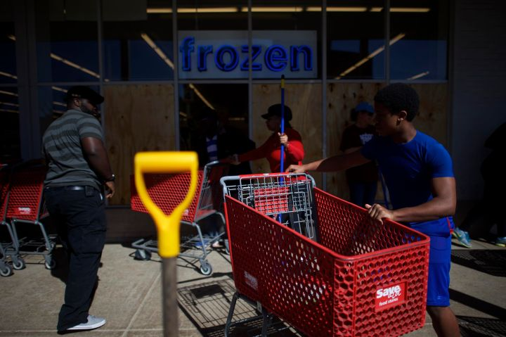 Friends and pedestrians help clean up a looted store in Baltimore.