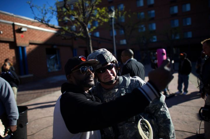 A man takes a selfie with a National Guard Officer Tuesday morning as others help clean up the city.