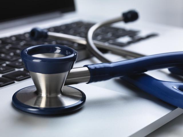 Stethoscope sitting on laptop illustrating online healthcare and doctor's desk