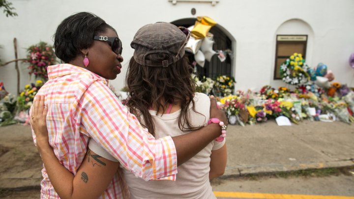 Charleston natives comfort each other during the church's first service since the shooting on June 17.