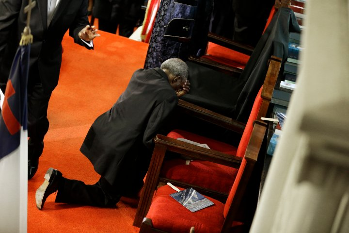 A parishioner prays at the empty seat of the Rev. Clementa Pinckney at the Emanuel AME Church.