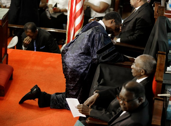 The Rev. Norvel Goff, right, prays at the empty seat of the Rev. Clementa Pinckney.
