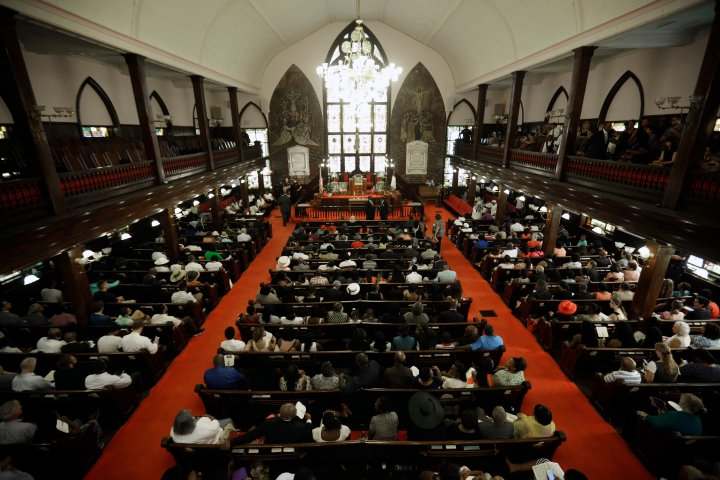 Parishioners sit at Emanuel AME Church four days after a mass shooting that claimed the lives of its pastor and eight others.