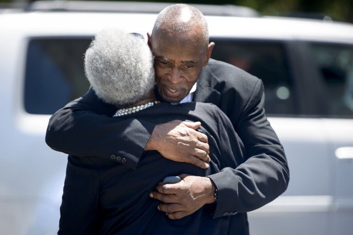 People embrace as they depart the Emanuel AME Church following Sunday services.