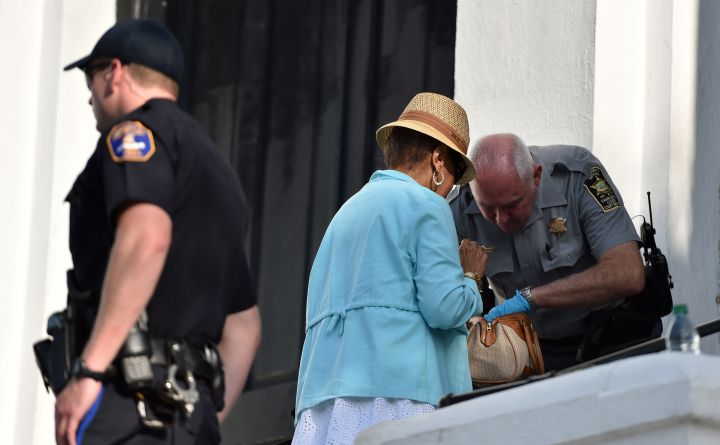 A Charleston County sheriff's deputy checks bags as people line up to enter for Sunday service at the Emanuel AME Church.