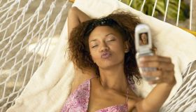 Woman in hammock taking picture with camera phone, puckering lips