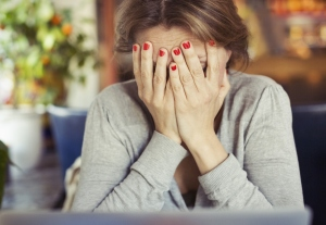 Sad young woman sitting with head in hands at home