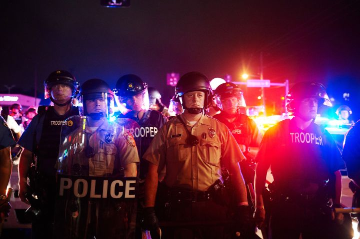 2015: Police stand to maintain the crowd after shots rang out on the anniversary of Mike Brown's death.