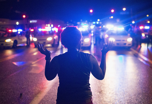 2015: A woman stands before police with her hands up in the air.
