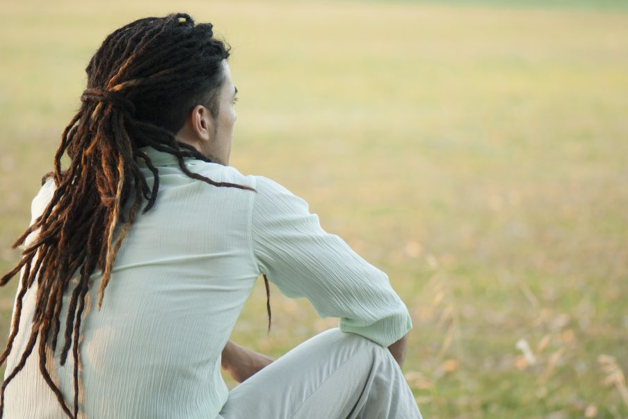 Man with dreadlocks sitting outdoors, rear view