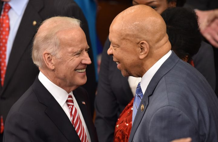 Biden greets civil rights leader and US representative John Lewis as they wait for the president.