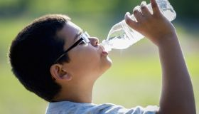 Nine year old boy drinking water from a bottle