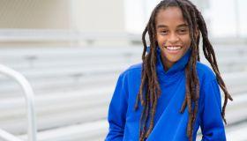 Mixed race boy smiling on bleachers
