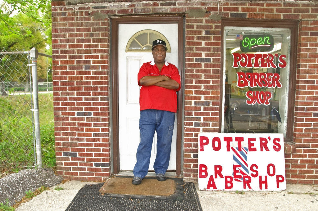 Barbershop owner in front of his own Barber Shop in Pensacola, Florida, USA