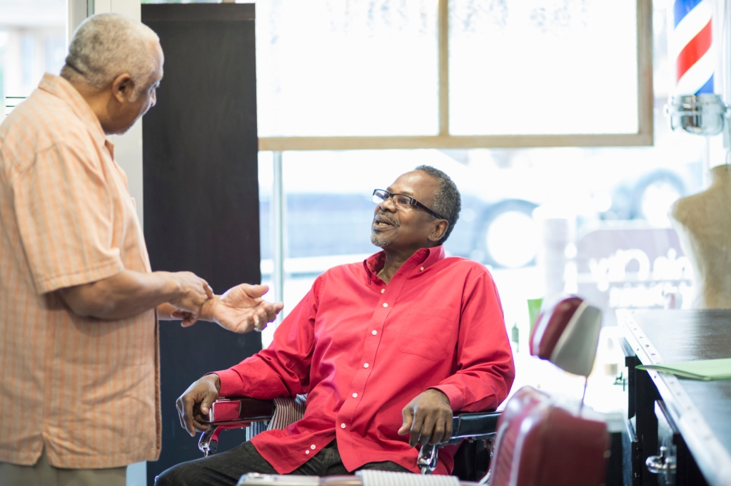 Black businessmen talking in retro barbershop
