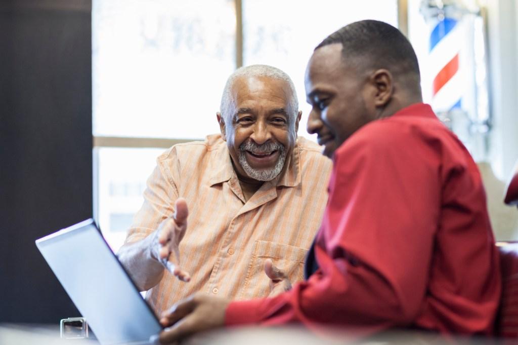 Black businessmen using laptop in retro barbershop