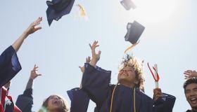 Graduates tossing caps into the air